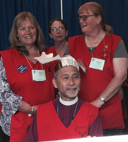 Diane Pound (upper left) helps Utah's Bishop Hayashi get suited up appropriately to serve as a General Convention volunteer for a day.